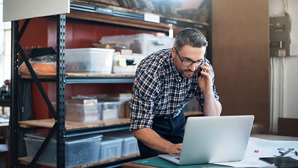 Man On Laptop In Warehouse